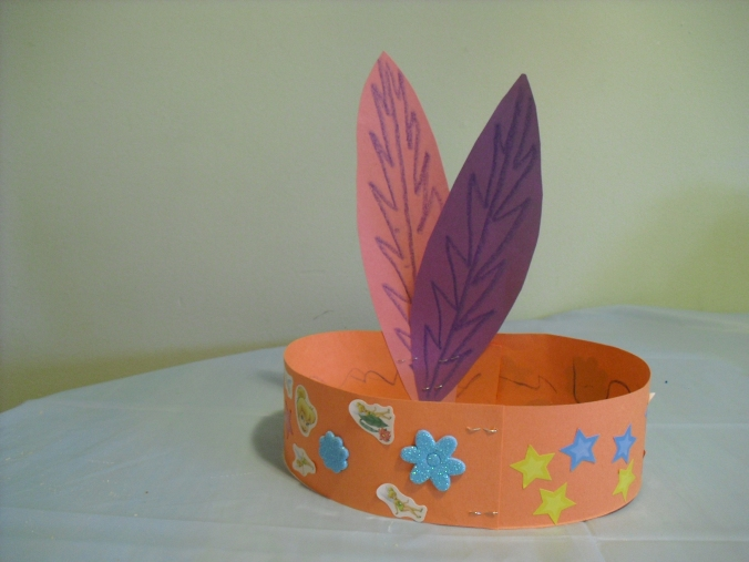 One sheet of construction paper and two long strips stapled together. Cut out feather shapes. Crayons and pretty glittery stickers! Staple to fit the child's head. Their all crowned princesses!